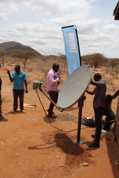 "Engineers install Liquid Telecoms' ""most robust"" VSAT dish on a metre high pole in the Kenyan village of Kiltamany."